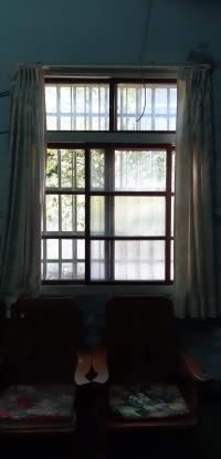 阿嬤從床上攬鏡高舉,對著窗戶望窗外的馬路,映照出阿嬤許多的盼望。昔日的空曠,今日樓層屋遮住田野風光和巷道